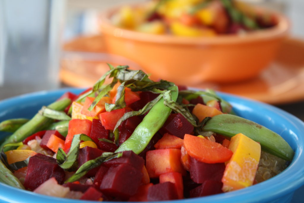 This Buddha Bowl features steamed beets, sweet potatoes, sugar snap peas, carrots, summer squash, corn, and fresh basil.
